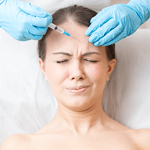 Woman receiving Botox injection on her forehead